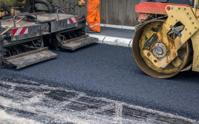 Asphalt paver machine during road construction, road construction crew apply the first layer of asphalt.