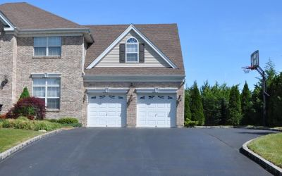 Brick suburban two car garage home with basketball hoop on blacktop driveway under clear blue daytime sky