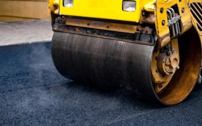 Compact steamroller flatten out the asphalt.